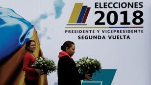 Los trabajadores llevan flores junto a un colegio electoral en Corferias antes de la segunda vuelta de las elecciones presidenciales en Bogotá, Colombia. 16 de junio de 2018.
