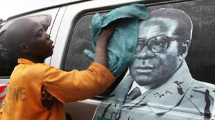 Un joven lava un minibús adornado con la imagen del presidente Robert Mugabe en una terminal de autobuses en Harare, Zimbabwe, 15 de noviembre de 2017