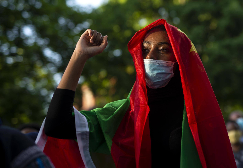 L'indignation a gagné les frontières éthiopiennes car une femme arbore un drapeau oromo lors d'une manifestation contre la mort du musicien et activiste Hachalu Hundessa devant le palais du gouverneur le 30 juin 2020 à St Paul, Minnesota.