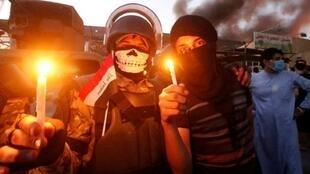 متظاهران عراقيان أمام مبنى حكومي تشتعل فيه النيران في البصرة في 6 أيلول/سبتمبر.
