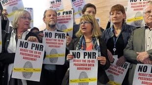 Des manifestants hostiles au PNR brandissent des pancartes pour dénoncer des atteintes aux libertés civiles.