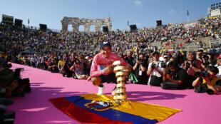 """Le cycliste équatorien Richard Carapaz, vainqueur du Giro 2019, pose avec le """"Trophée sans fin"""" (Trofeo Senza Fine) lors de la cérémonie de podium, le 2 juin 2019 à Vérone."""