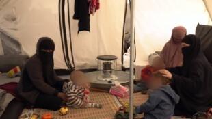 """نساء من تنظيم """"الدولة الإسلامية"""" مع أطفالهن بعد فرارهن من الباغوز شرق سوريا"""