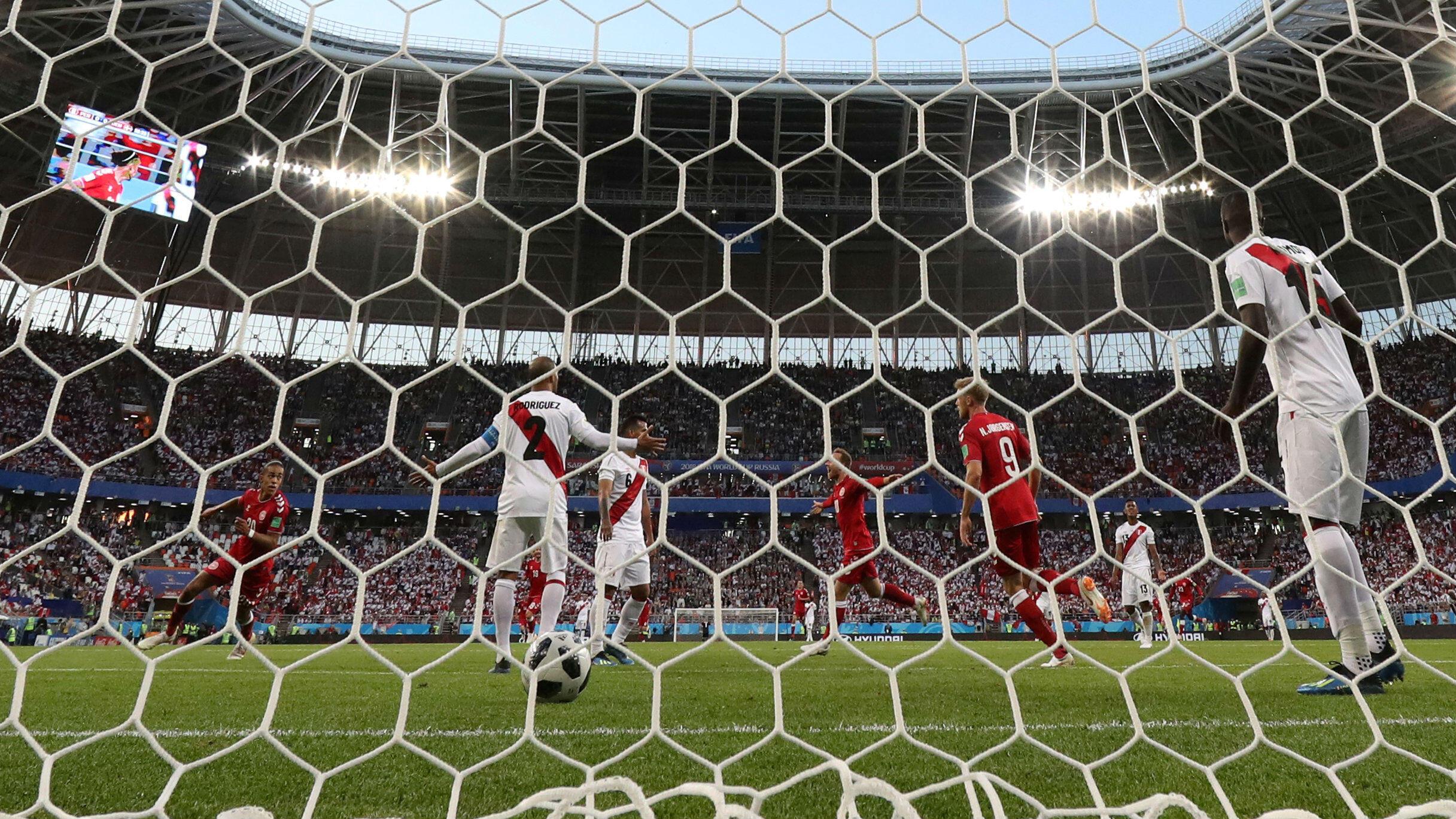 El danés Yussuf Poulsen celebró su primer gol con Christian Eriksen, mientras el peruano Alberto Rodríguez y sus compañeros de equipo parecen abatidos.