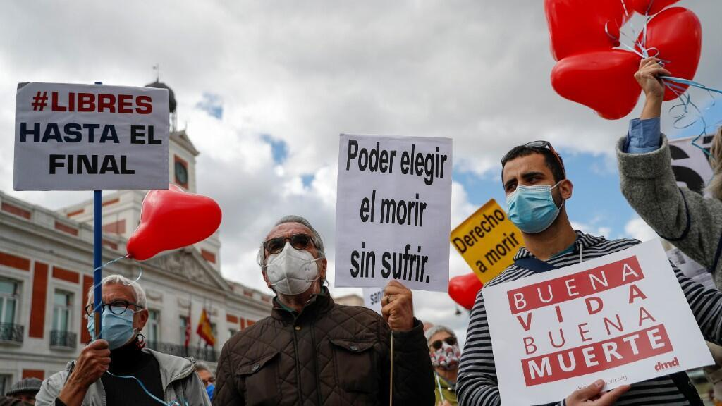 """Supporters of the law for the regulation of euthanasia hold signs that say """"good life, good death"""", """"free until the end"""", """"choose to die without suffering"""" while participating in a demonstration in front of the parliament during the plenary session of Spain to vote on the euthanasia law in Madrid, Spain, March 18, 2021."""