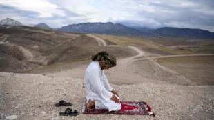 أفغاني يؤدي الصلاة على هضبة قرب مدينة مزار الشريف في شمال أفغانستان في 15 أيار/مايو 2020.