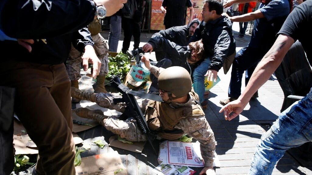 Un soldado chileno es derribado por manifestantes durante las protestas contra el Gobierno de Sebastián Piñera en Valparaíso, Chile. 21 de octubre de 2019.