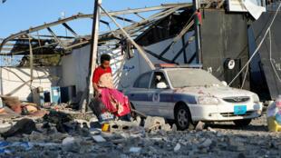 Un migrante recoge ropa entre los escombros que dejó el ataque aéreo en el suburbio de Tajoura, en la capital libia Trípoli, el 3 de julio de 2019.
