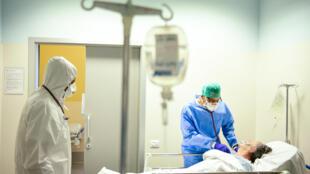 مريضة وعاملان صحيان في مستشفى في بيرغامو في إيطاليا في 3 نيسان/أبريل 2020