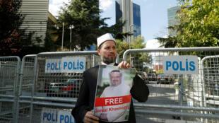 Un manifestant tient une pancarte à l'effigie de Jamal Khashoggi devant le consulat saoudien d'Istanbul, le 5 octobre 218.