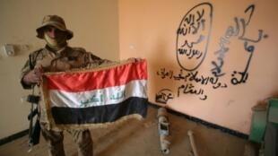 """جندي عراقي يحمل العلم الوطني داخل مقر لتنظيم """"الدولة الإسلامية"""" خلال عملية تطهير حي الضباط في الفلوجة"""
