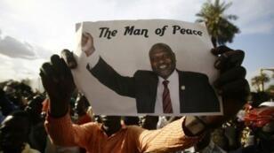 رجل يرفع صورة رياك مشار في الخرطوم بتاريخ 5 آب/أغسطس 2018
