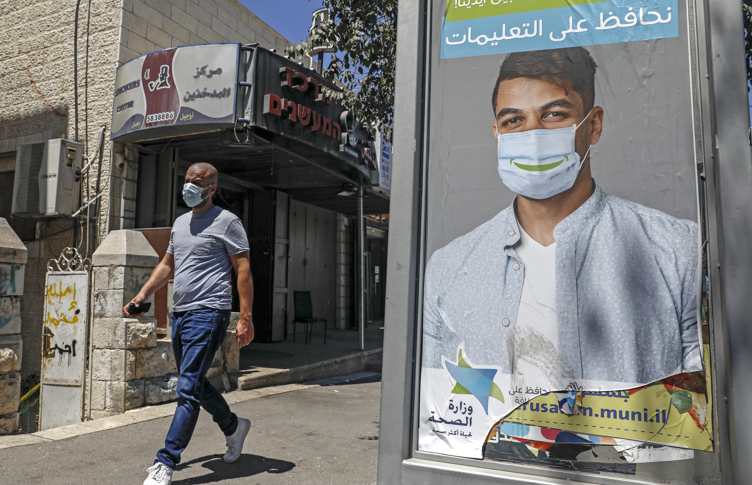 A mask-clad man walks past a billboard showing other mask-clad faces and adequate social distance measures, raising awareness about Covid-19 coronavirus pandemic precautions, in the Beit Hanina neighbourhood in Israeli-annexed East Jerusalem, on August 17, 2020.