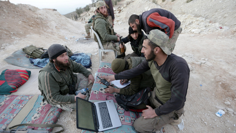 Combatientes del Ejército sirio libre apoyados por Turquía se sientan juntos en el campo de Afrin oriental
