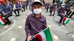 تلاميذ ايرانيون يضعون كمامات ويحملون العلم الايراني ملتزمين التباعد الجسدي في مدرسة بالعاصمة طهران في الخامس من ايلول/سبتمبر 2020