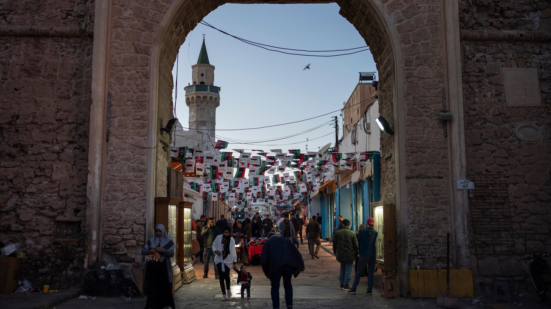 En esta foto del 25 de febrero de 2020, la gente camina cerca de una de las entradas de la Ciudad Vieja en Trípoli, Libia.