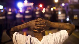 Un manifestant fait face à la police à Baltimore, le 28 avril au soir, alors que le couvre-feu a été décrété dans la ville.