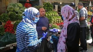 امراتان تشتريان الخضار في سوق في العاصمة الأردنية عمّان، 23 نيسان/ابريل 2020