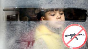Un niño mira a través de la ventanilla de un autobús durante la evacuación de la ciudad sitiada de Douma, Guta Oriental, en Damasco, Siria, el 13 de marzo de 2018.