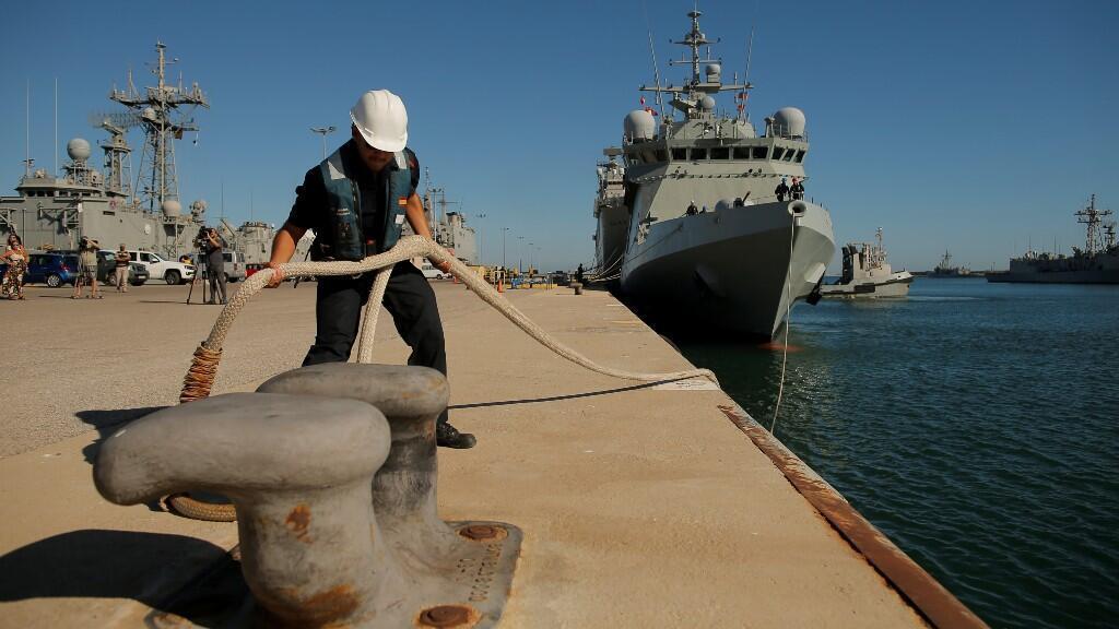 """Un miembro del barco militar español """"Audaz"""" retira la cuerda antes de que salga de la base naval de Rota,en el sur del país, después de que el Gobierno español anunciase que el barco se dirigirá a la isla italiana de Lampedusa."""
