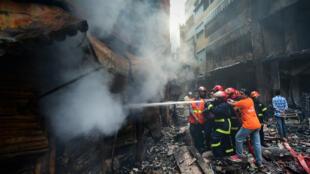 Des pompiers essayent d'éteindre l'incendie, le 21 février, à Dacca, au Bangladesh.