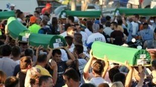 - بوسنيون يحملون نعوشا تحتوي رفات 136 شخصا من ضحايا مجزرة سربرنيتشا في 10 تموز/يوليو2015