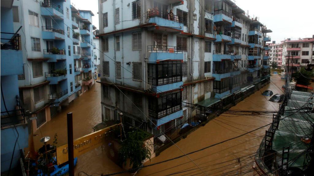Los residentes miran desde un balcón a la colonia inundada en Katmandú, Nepal, el 12 de julio de 2019.