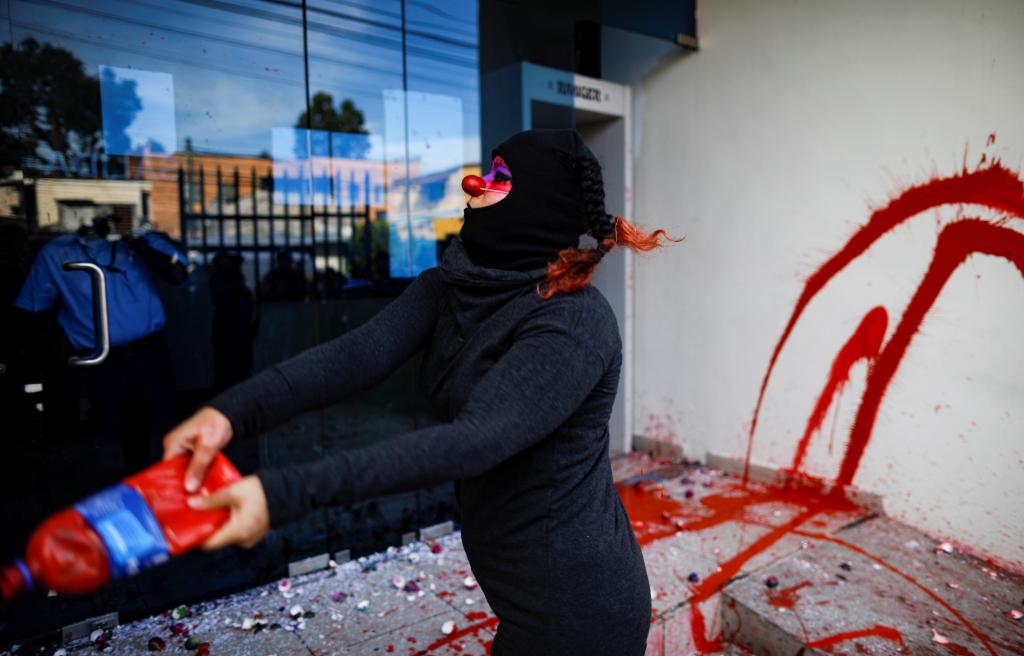 Una mujer tira pintura en la entrada de la Fiscalía en San Salvador.