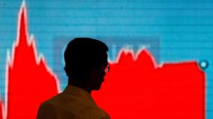 Un hombre pasa frente a una pantalla que muestra las noticias de la actualización de los mercados dentro del edificio de Bombay Stock Exchange (BSE) en Mumbai, el 6 de febrero de 2018.