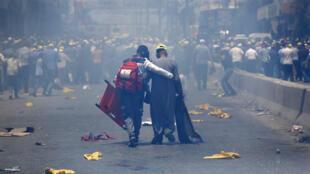 مسعف من الصليب الأحمر الفلسطيني يساعد متظاهرا مصابا