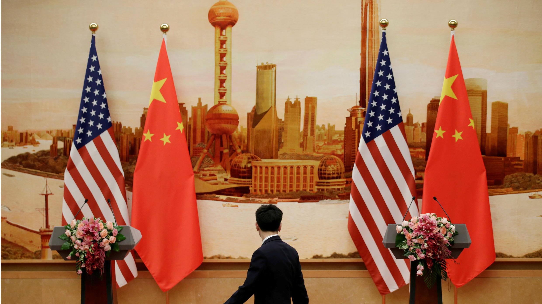 Un miembro del personal camina frente a banderas estadounidenses y chinas colocadas para una conferencia de prensa conjunta por el Secretario de Estado de Estados Unidos, Mike Pompeo, y el ministro de Relaciones Exteriores de China, Wang Yi, en el Gran Palacio del Pueblo en Beijing, China. 14 de junio de 2018.