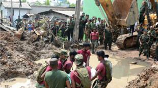 Des soldats sri lankais tentent de retrouver des survivants dans l'immense décharge d'ordures de Kolonnawa entourée de bidonvilles à la limite nord-est de la capitale Colombo