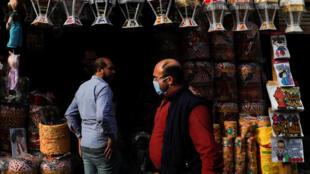 رجل يرتدي قناعا طبيا أمام متجر لبيع نظر فوانيس رمضان، قبل شهر رمضان المبارك في الخيامية، شارع في القاهرة القديمة، مصر 16 أبريل/ نيسان  2020.