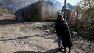 Dos residentes se abrazan mientras están parados cerca de una casa incendiada por los armenios que partieron, en un área que había estado bajo su control militar, pero que pronto será entregada a Azerbaiyán, en la aldea de Cherektar, en la región de Nagorno Karabaj, 14 de noviembre de 2020.