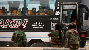 Los rebeldes y civiles sirios miran por la ventanilla de un autobús cuando salen de Harasta en la región de Guta Oriental, en Damasco, Siria, el 23 de marzo de 2018.