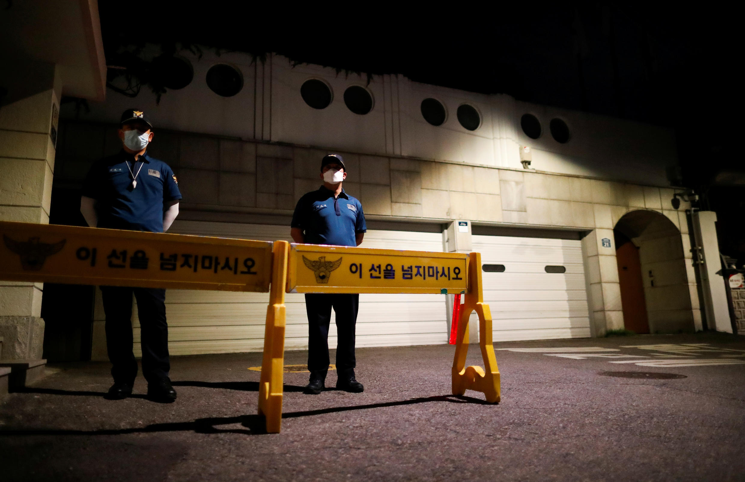 Police officers stand guard in front of the residence of Seoul Mayor Park Won-soon as rescue workers conduct a search operation in Seoul, South Korea, July 10, 2020.