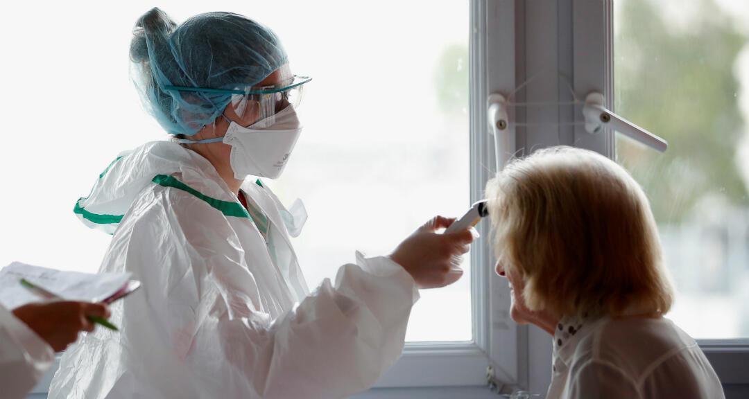 Una enfermera con equipo de protección y mascarilla facial, verifica la temperatura de un paciente en el hospital privado Clinique Breteche en Nantes, el 30 de abril de 2020.