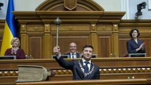 Ukraine's President Volodymyr Zelensky holds the Bulava, the Ukrainian symbol of power, during his inauguration ceremony at the parliament in Kiev on the same day that Russia wanted to convene a UN Security Council meeting on Ukraine's language law
