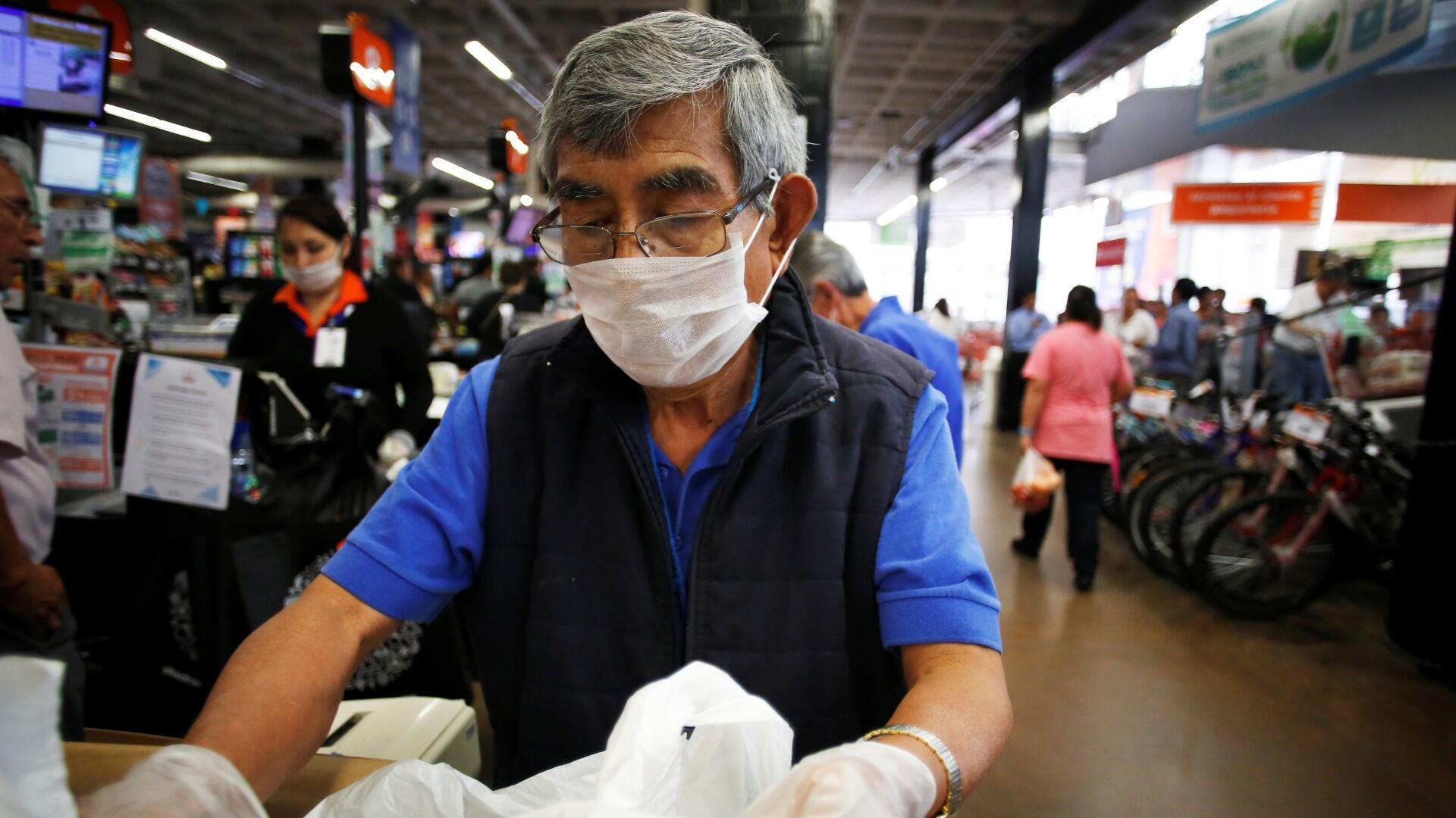 Un anciano, que trabaja como empacador en un supermercado, usa una mascarilla protectora como medida de seguridad para la enfermedad por coronavirus (COVID-19), en la Ciudad de México, México, 17 de marzo de 2020. Fotografía tomada el 17 de marzo de 2020.