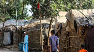 Rohingya refugees walk past a red flag used to mark the house of a resident infected with coronavirus in a sprawling camp on the Bangladesh-Myanmar border housing nearly a million people