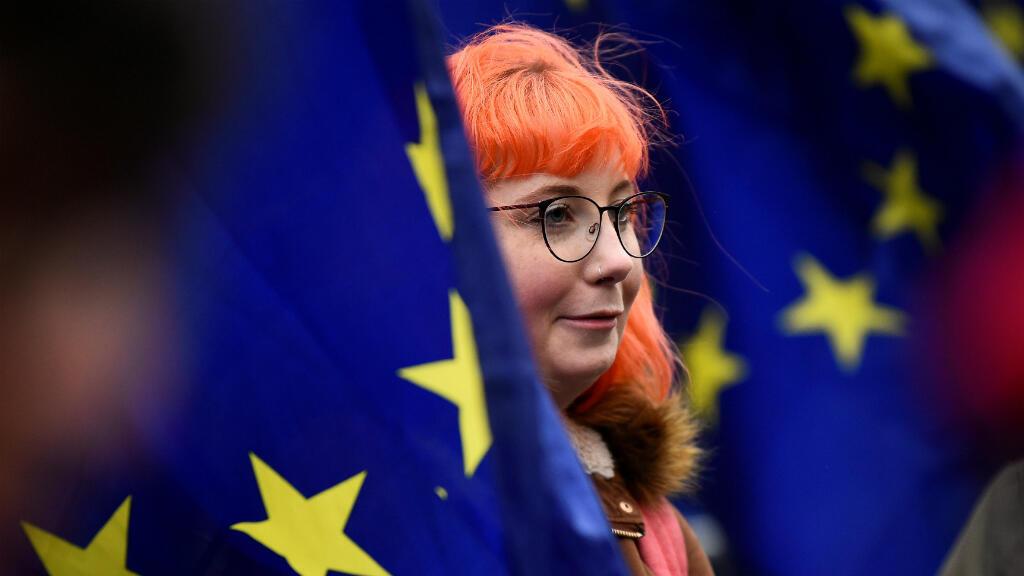 Un manifestante se encuentra entre las banderas de la Unión Europea fuera de las Casas del Parlamento, luego de que se rechazara el acuerdo del Brexit de la primera ministra Theresa May ,en Londres, Reino Unido, el 16 de enero de 2019.