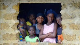 Des habitants du village de Banjol, au Liberia, regardent une équipe sanitaire emporter le corps de leur voisin, victime d'Ebola.