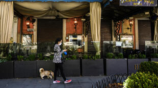 A woman walks her dog past Harry's Bar on Via Veneto in central Rome, which was closed despite an easing of the coronavirus lockdown