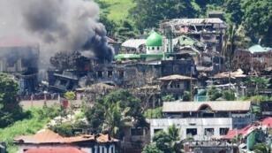 منزل يحترق بعد قصف مواقع لناشطين إسلاميين يتحصنون في مدينة مراوي المسلمة في جنوب الفلبين في 26 حزيران/يونيو 2017