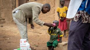 Un travailleur social dispense à un enfant un médicament pour la chimioprévention du paludisme saisonnier (CPS)  dans le village de Goundri, au nord-est de Ouagadougou, la capitale du Burkina Faso, le 20 août 2019.
