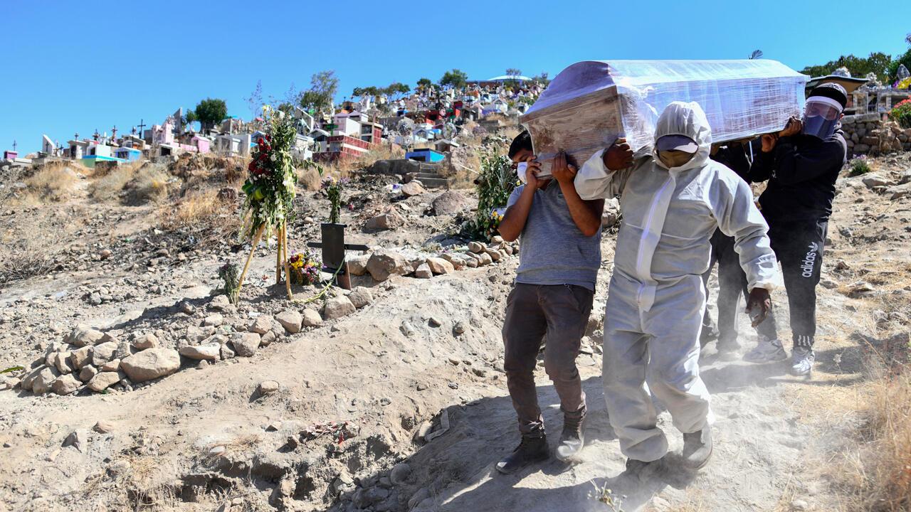 Personas entierran a un familiar en un espacio excavado para las víctimas de Covid-19 en un cementerio en el distrito rural de Paucarpata, cerca de la ciudad de Arequipa, al sur de Perú, el 3 de agosto de 2020.