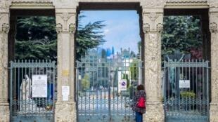 Una mujer mira dentro del Cementerio de Bérgamo, Lombardía, el 20 de marzo de 2020, en medio de la pandemia en Italia.