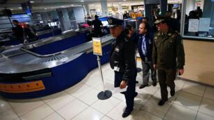 El general de la Fuerza Aérea de Chile y director de aeronáutica Víctor Villalobos, junto al general de la policía Leonardo Espinoza, inspeccionan el área de salidas dentro del aeropuerto internacional de Santiago de Chile.