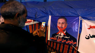 An Iraqi demonstrator takes a photo of a poster of Assaad al-Aidani, the governor of Basra and a candidate for the prime minister's office during ongoing anti-government protests in Baghdad on December 26, 2019.
