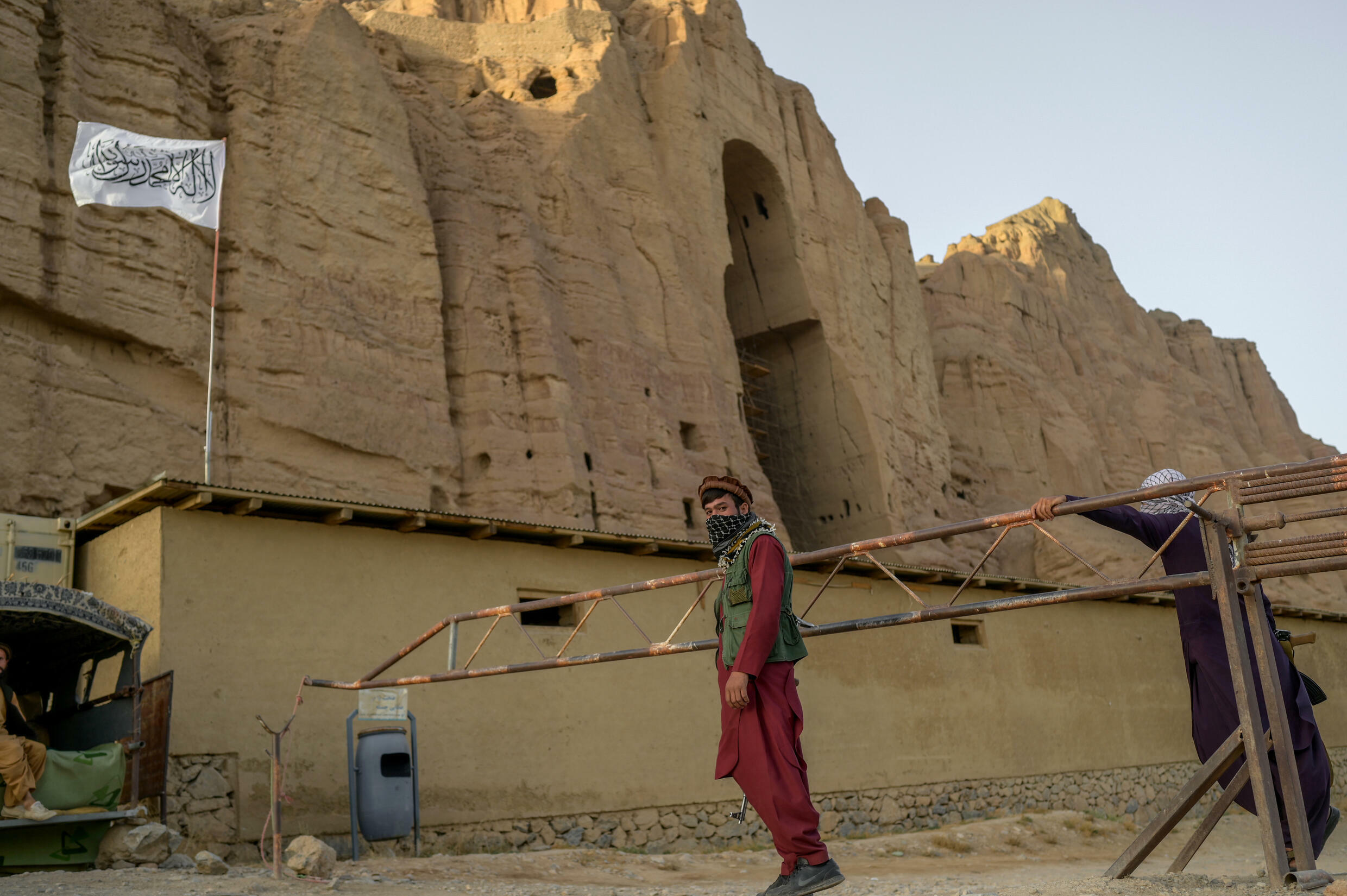 The Taliban fly their flag at the site where a Buddha statue once stood, before it was destroyed by the former militant regime